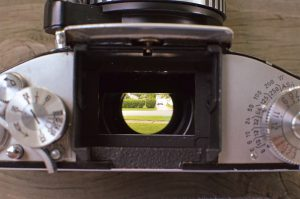The viewfinder has it's own ground glass, so when you remove it, you look directly into the mirror box.