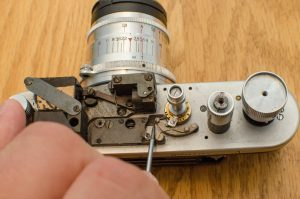 I am pointing to the black sliding lever which keeps the second curtain open when a the slow speed governor is engaged. When the governor is removed, this lever will always prevent the second curtain from closing unless you slide it towards the viewfinder.