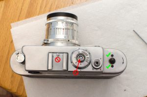 Only remove the two black screws with the green checks. Do not remove the screw in the accessory post or the large screw inside of the film speed shaft.