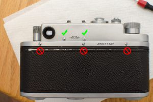 Only remove the two green screws. Do not remove any of the three red screws on the lower plate.