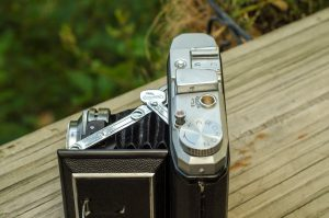 The metal tab with the Kuribayashi logo appears on both sides of the camera. You press on this tab to close the camera.