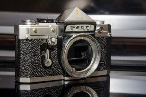 The Petri breech-lock bayonet mount required the lens to be installed upright, and then the chrome ring around the front of the camera would be rotated to lock the lens into place.