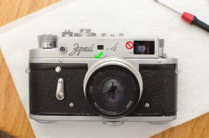 The screw to the left of the main viewfinder window hides the horizontal rangefinder adjustment on the Zorki 4.