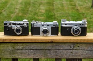 The Clarus next to an Argus C3 and Perfect One oh Two. The Clarus is wider than the Argus, but shorter than either other camera.