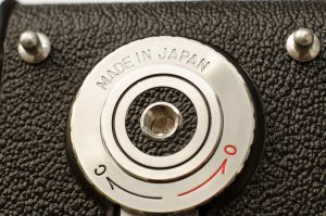 "The last of the Yashica-Ds had a black plastic locking knob and some were made in Hong Kong.  My example still has the metal chrome knob with ""Made in Japan"" engraved into the metal."